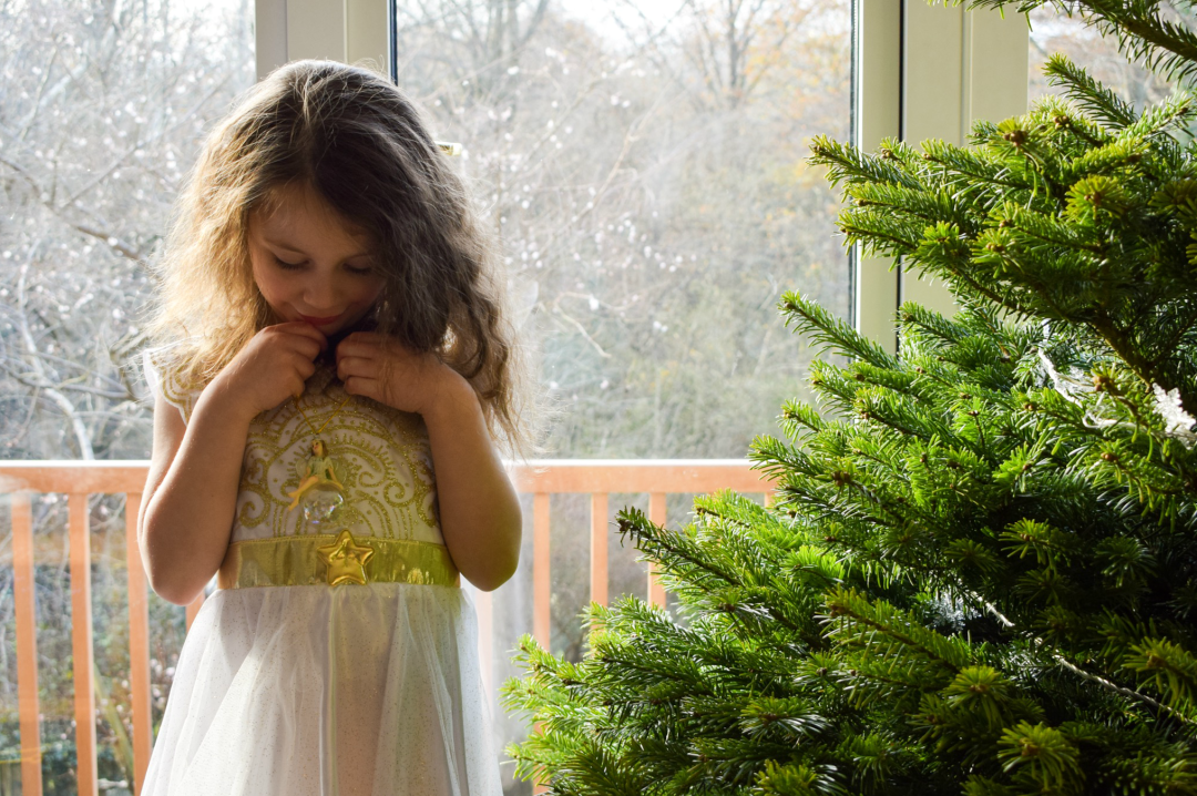 A photograph of a young girl wearing an angel costume and standing by a Christmas tree and holding a fairy Christmas tree ornament - Photographs of decorating our Christmas tree - Our Christmas Tree Day - Mrs H's favourite things