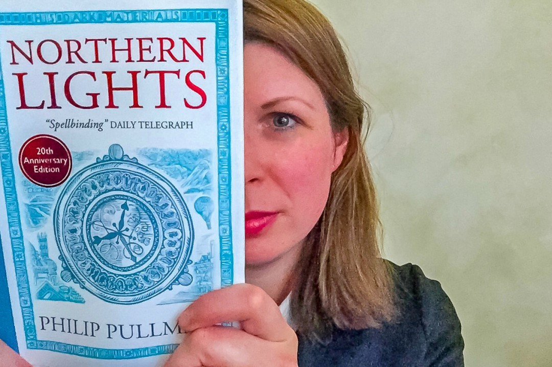 "A photograph of a brunette lady holding a hardback copy of the book ""Northern Lights"" by Philip Pullman - She is peeking from the side of the book - For the Love of Books - Mrs H's favourite things"
