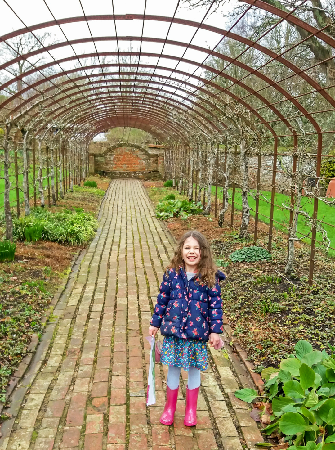 A photograph of a little girl standing in an arbor in the garden of the National Trust property Bateman's - Our Weekend Happy #3 - A love manifesto, lazy days & a pub quiz - Mrs H's favourite things
