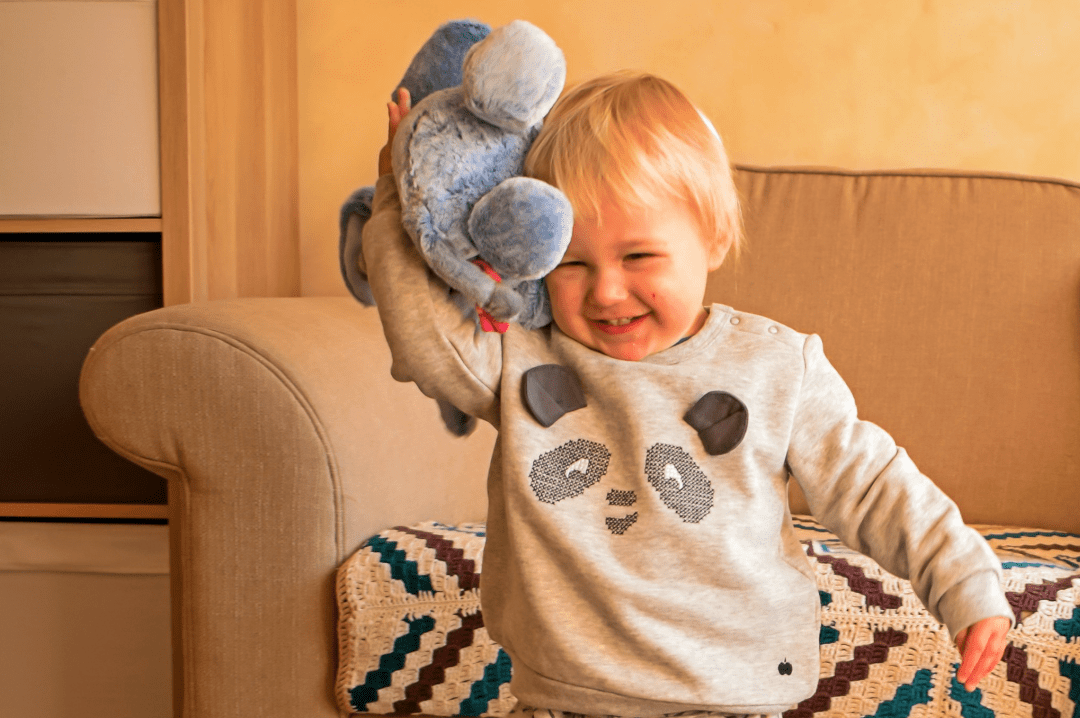 A photograph of a little boy happily snuggling and cuddling the Snuggletime Eeyore from Posh Paws Snuggletime Winnie the Pooh Range of toys - Snuggletime Winnie the Pooh Range - A Review - Mrs H's favourite things