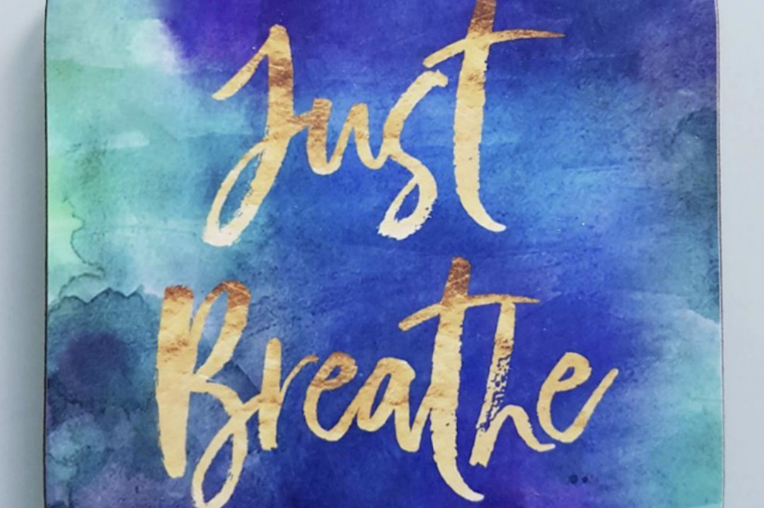 "A photograph of a coaster, with a blue water colour effect on and the words ""just breathe"" - A Few Hours of Self-Care - A Review of The Space Retreat - Mrs H's favourite things"