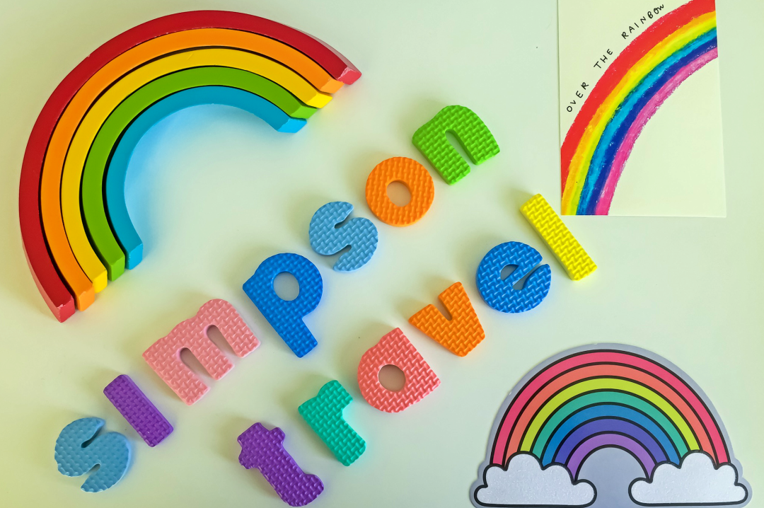 "A photograph of a wooden rainbow toy (showing only the red, orange yellow, green and blue arc of the rainbow), two postcards of rainbows and foam letters spelling out ""Simpson Travel"" - Chasing Rainbows with Simpson Travel - Mrs H's favourite things"
