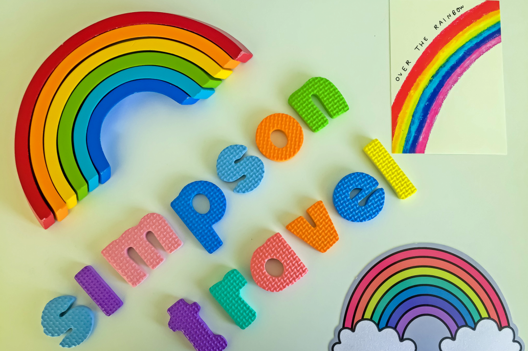 "A photograph of a wooden rainbow toy (showing only the red, orange yellow, green, blue and indigo arc of the rainbow), two postcards of rainbows and foam letters spelling out ""Simpson Travel"" - Chasing Rainbows with Simpson Travel - Mrs H's favourite things"