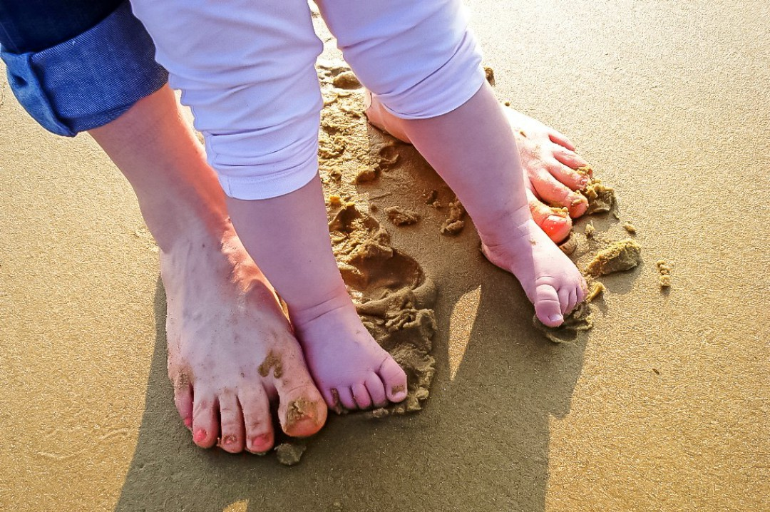 A photograph of the barefoot feet of a woman and her daughter as they walk along a sandy beach - Chasing Rainbows with Simpson Travel - Mrs H's favourite things