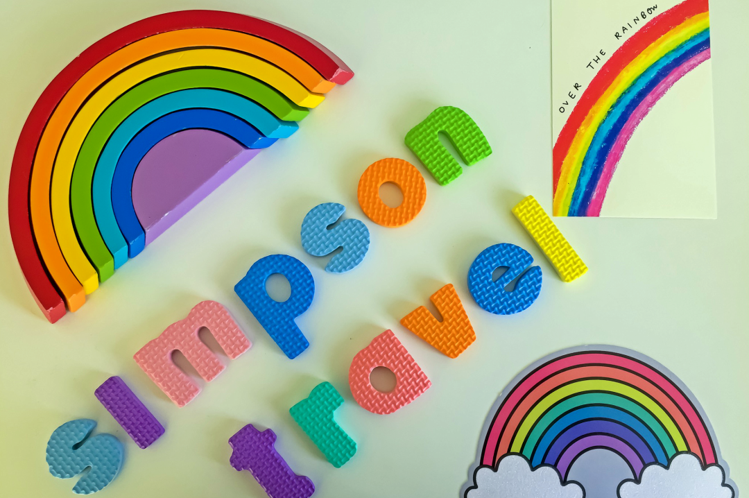"A photograph of a wooden rainbow toy (showing the full spectrum of the rainbow - red, orange, yellow, green, blue, indigo and violet), two postcards of rainbows and foam letters spelling out ""Simpson Travel"" - Chasing Rainbows with Simpson Travel - Mrs H's favourite things"