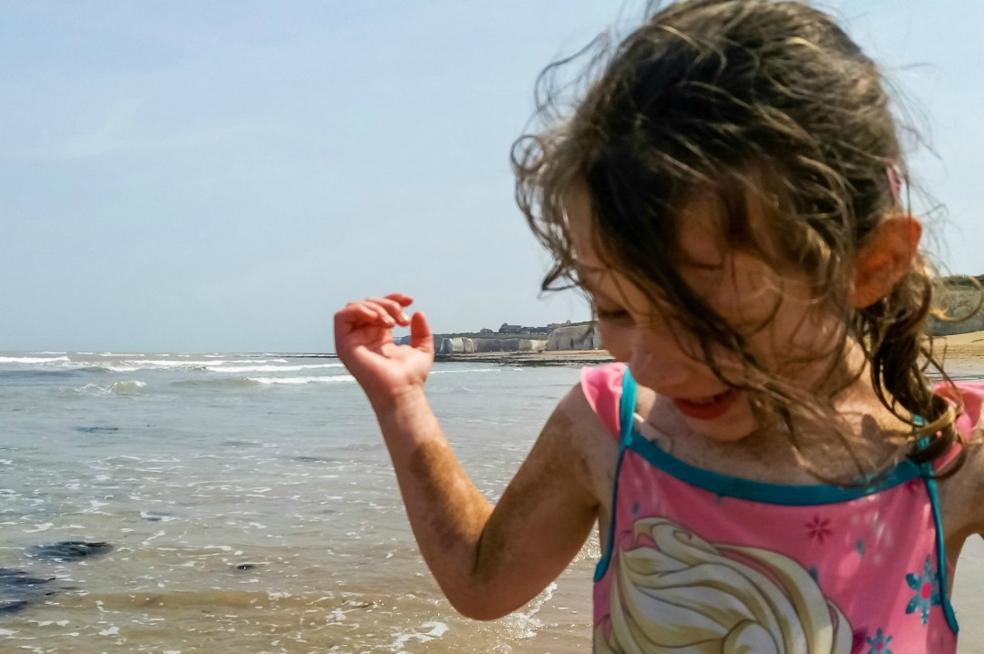 A photo of a little girl on a beach on a summer day - Five Reasons I'm Looking Forward to Summer - Mrs H's favourite things