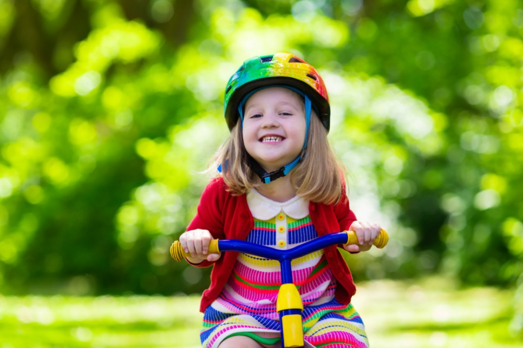 A photograph of a little girl smiling happily and wearing a rainbow striped dress and riding a trike - Tips on Buying Trikes for Toddlers - Mrs H's favourite things