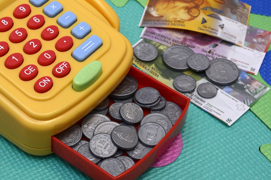 A photograph of a brightly coloured plastic child's toy till filled with and surrounded by toy coins and notes - 3 Ways To Save For Your Child's Future - Mrs H's Favourite Things