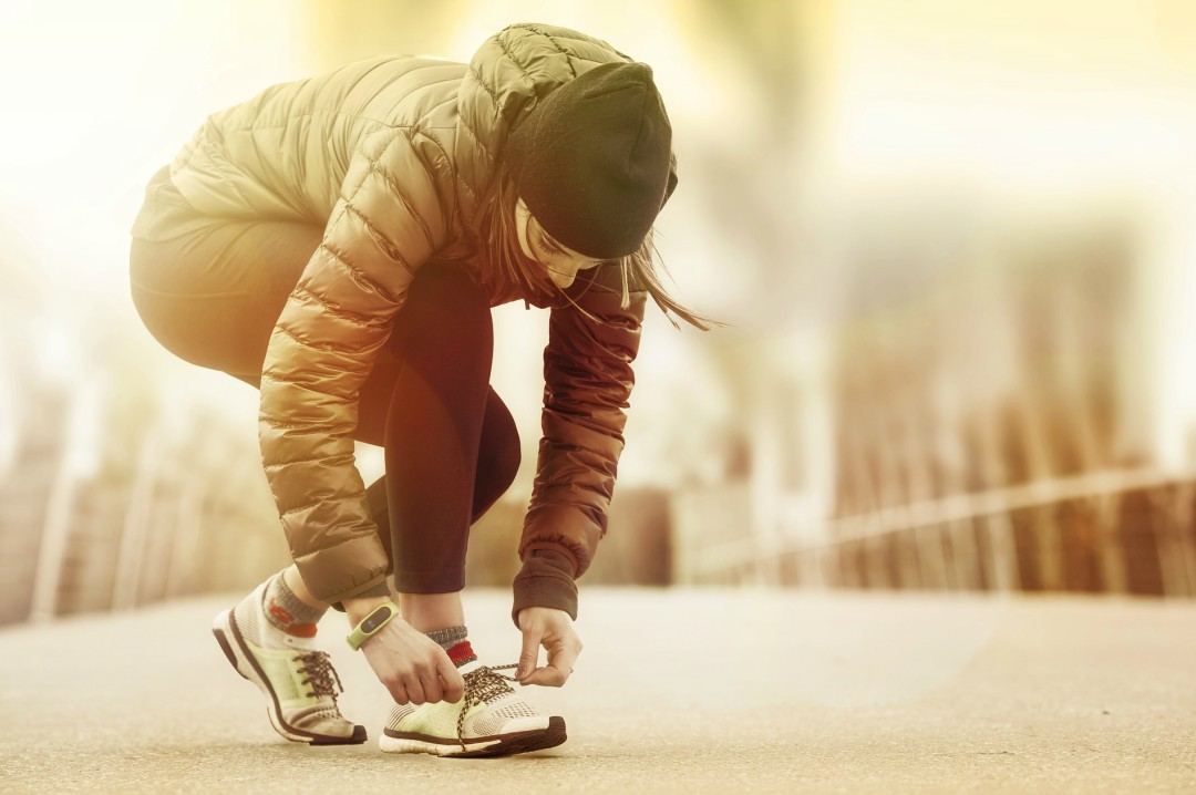 A photograph of a woman doing up her shoe laces while out on a run - Awesome Ways To Improve Your Mood - Mrs H's favourite things