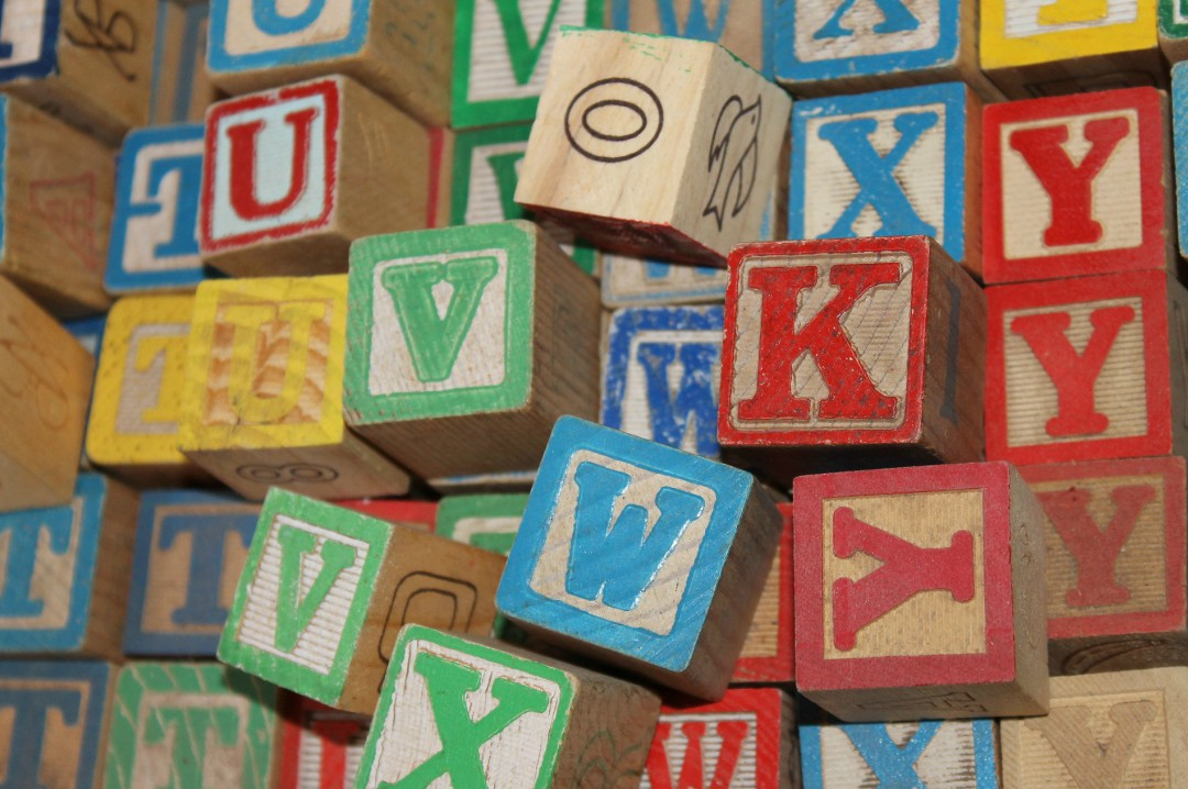 A photograph of a pile of colourful wooden building blocks with letters of the alphabet - Creating A Positive Learning Environment For Your Kids - Mrs H's favourite things