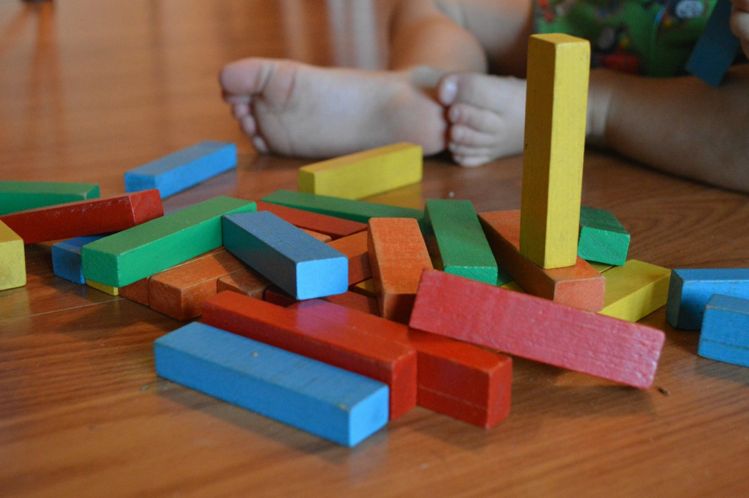 A photograph of a baby's feet and some colourful building blocks - Creating A Positive Learning Environment For Your Kids - Mrs H's favourite things