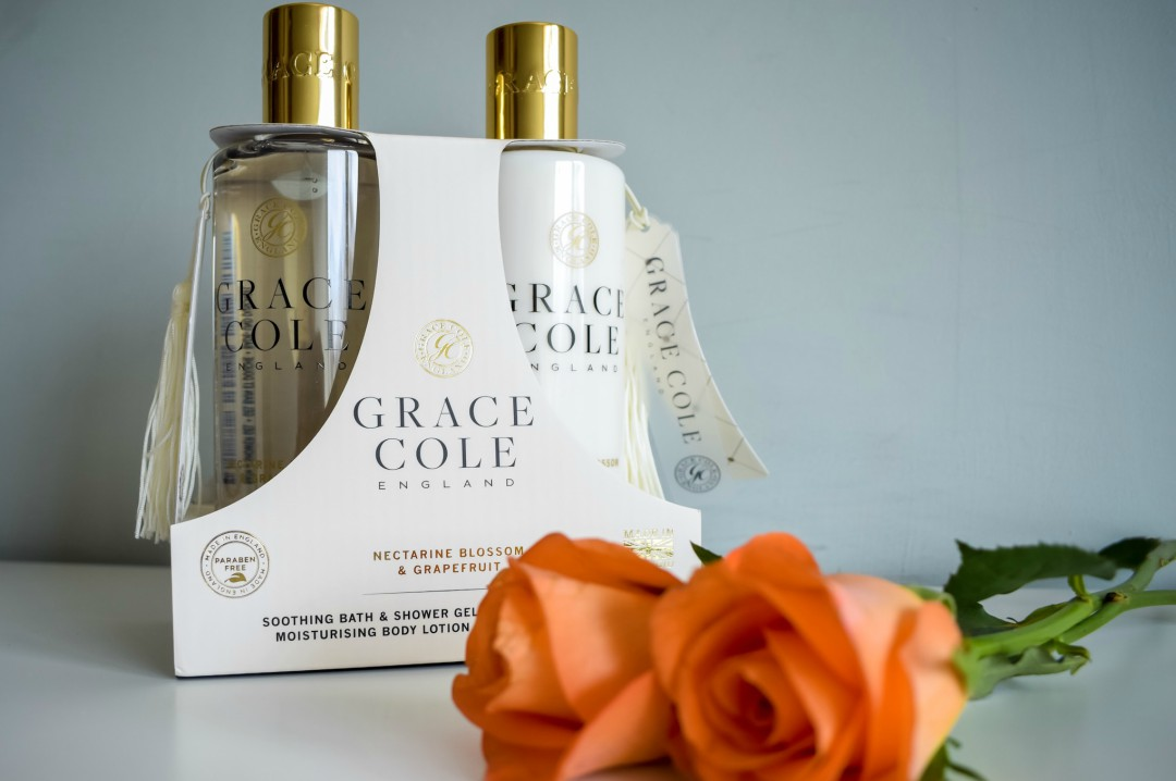 A photograph of the Grace Cole Body Duo in Nectarine Blossom & Grapefruit with 2 peach roses in front of it - Mother's Day Gift List - Treats for the Mother in your Life - Mrs H's favourite things