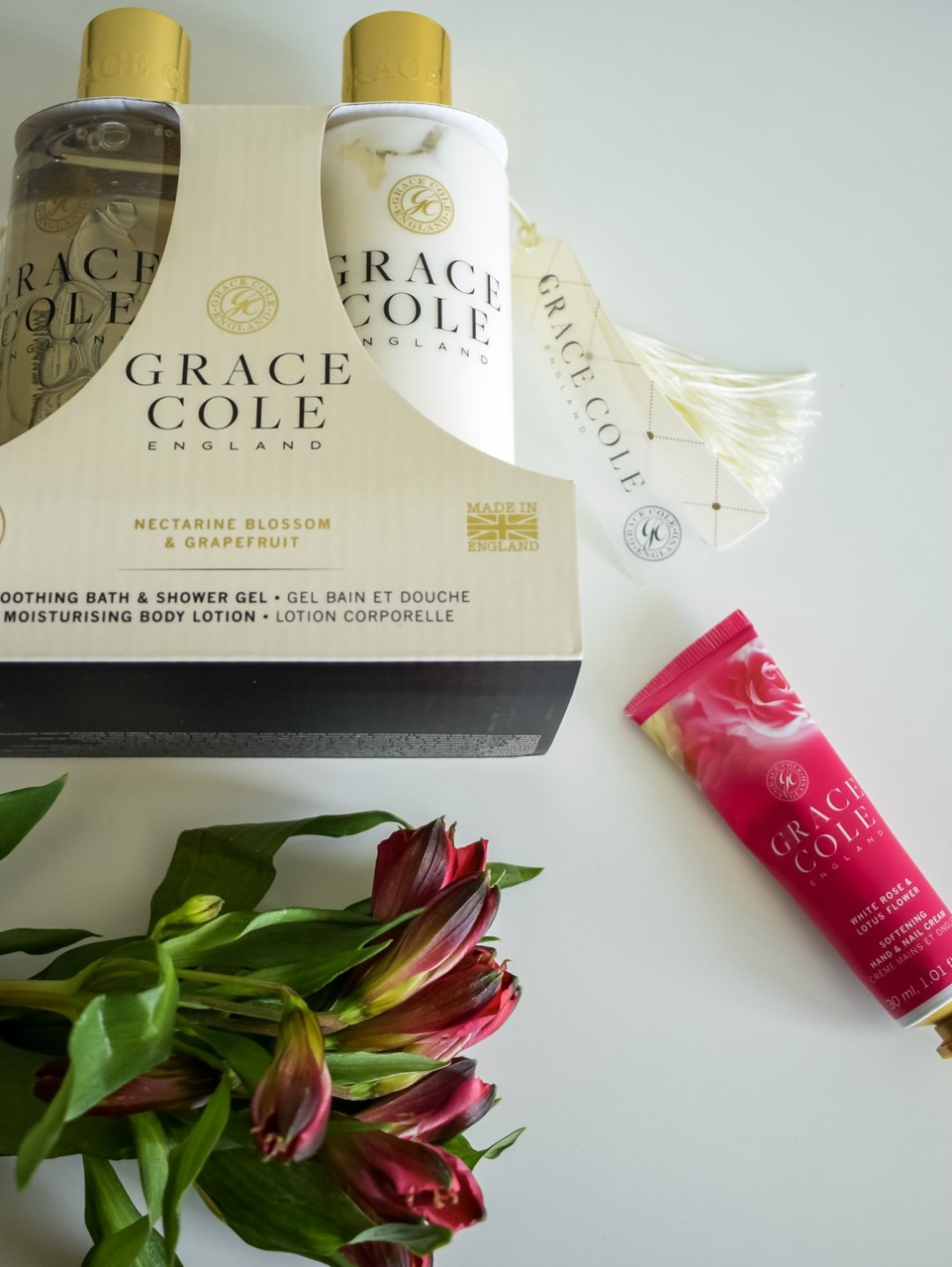 A photograph of the Grace Cole Body Duo in Nectarine Blossom & Grapefruit and a softening hand & nail cream in White Rose & Lotus Flower with a bunch of flowers - Mother's Day Gift List - Treats for the Mother in your Life - Mrs H's favourite things