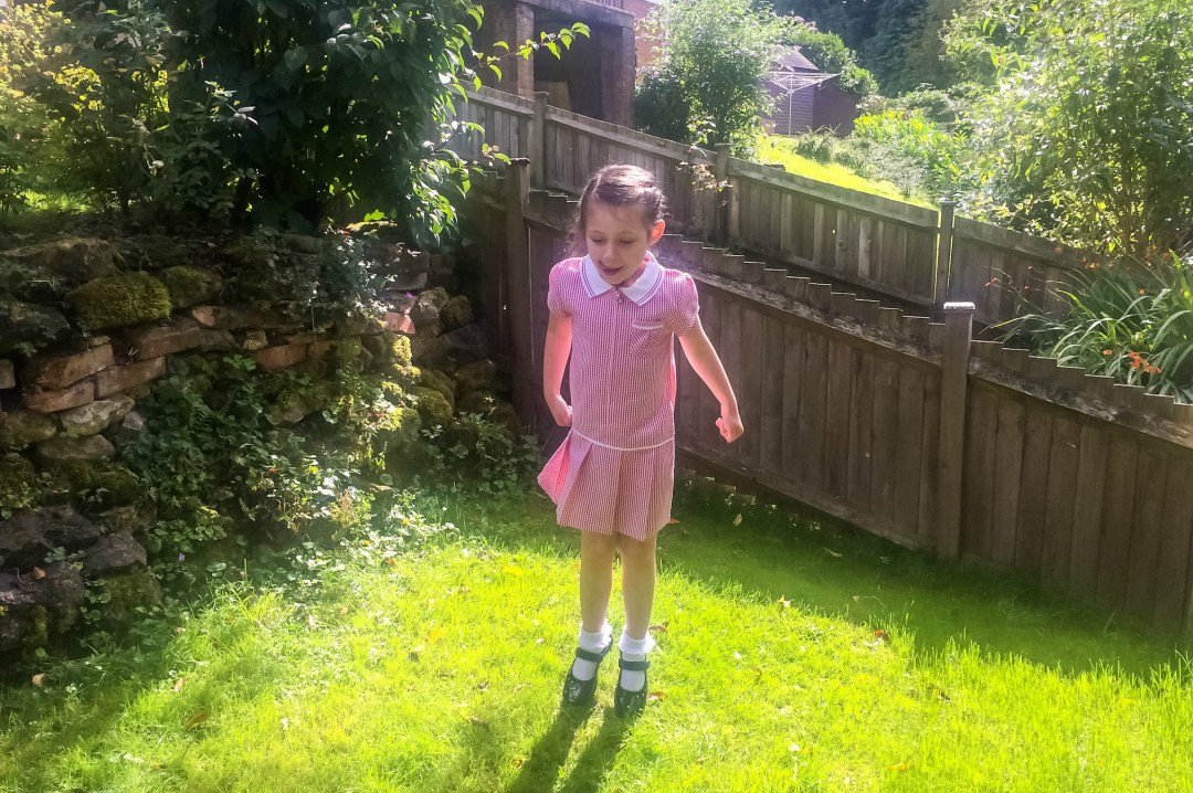 A little girl in her summer school uniform jumping up and down in the garden - A photograph of a mother holding her toddler boy's hand as they are walking in the sunshine- Why Back In Your Day No Longer Matters - Mrs H's favourite things
