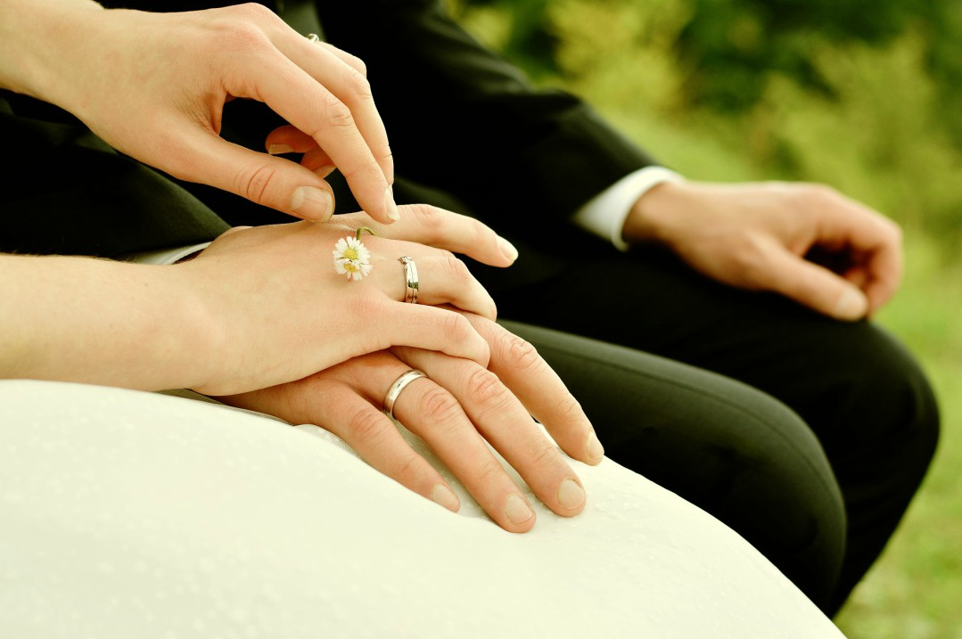 A photograph of a newly married bride and groom holding hands and showing off their engagement and wedding rings - How To Take Care Of Your Engagement And Wedding Rings - Mrs H's favourite things