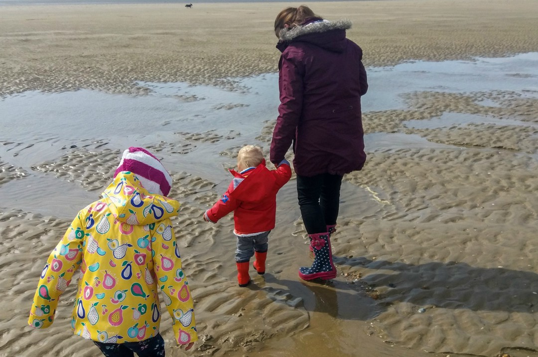 A photograph of a mum, her son and her daughter all dressed up in coats etc and paddling at Camber Sands - Our Weekend Happy - Pottering, A Beach Day & Seeing Auntie B _ Mrs H's favourite things