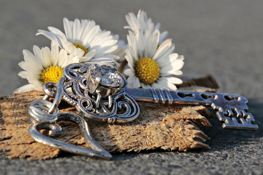 A photograph of an elaborate door key on a piece of wood and surrounded by daisies - What To Do When Moving Day Is Close - Mrs H's Favourite Things
