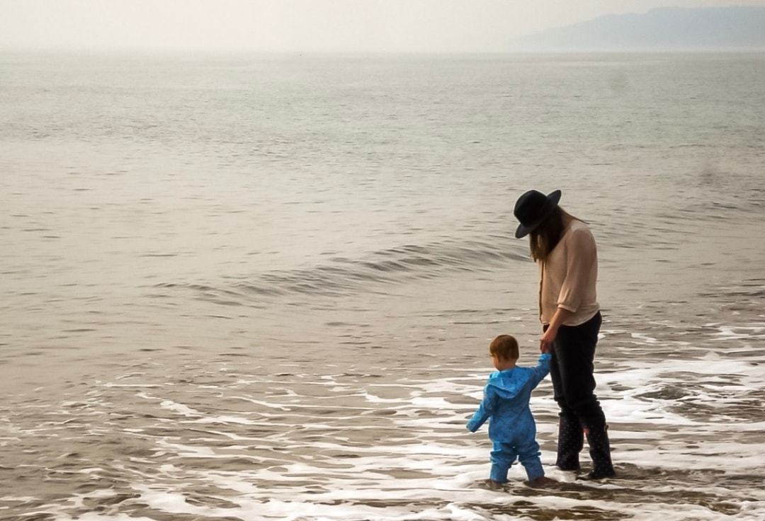 A photograph of a mother and her little girl paddling in the sea - Chronic Depression And Deciding To Become A Parent - Mrs H's favourite things