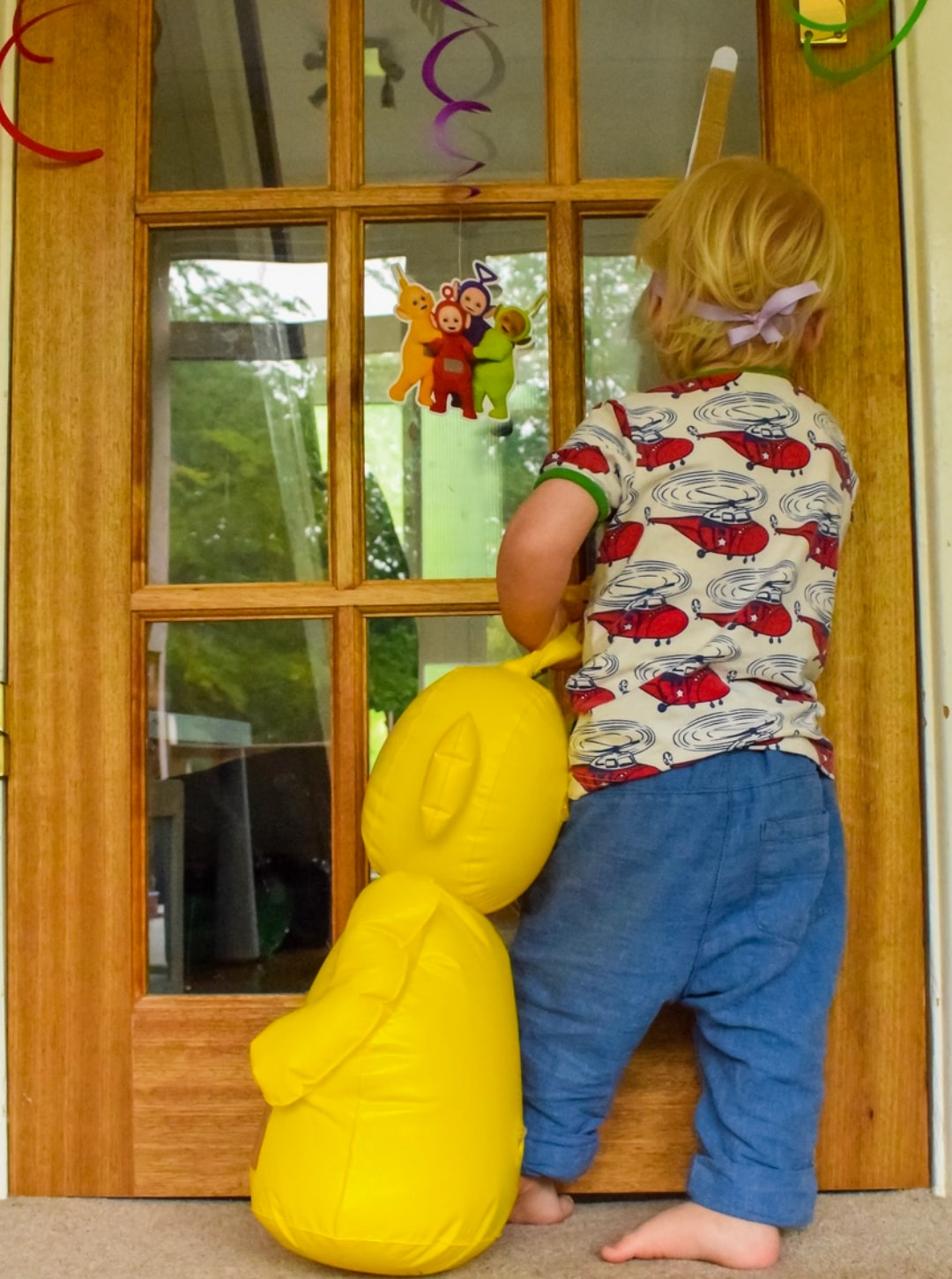 A photograph of a little boy standing in front of a door decorated with Teletubby party decorations and wearing a Laa-Laa Tubby Antennae which is part of the Teletubbies Playdate Pack - Hosting A Teletubbies Playdate #TubbyPlaydate - Mrs H's favourite things