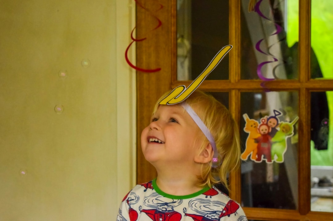 A photograph of a little boy standing in front of a door decorated with Teletubby party decorations and watching bubbles fall to the ground while wearing a Laa-Laa Tubby Antennae which is part of the Teletubbies Playdate Pack - Hosting A Teletubbies Playdate #TubbyPlaydate - Mrs H's favourite things