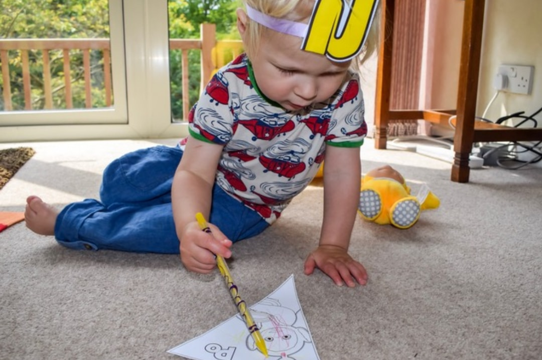 A photograph of a little boy wearing a Laa-Laa Tubby Antenna from the Teletubbies Playdate Pack and colouring in the Tubby Bunting which is also contained in that pack - Hosting A Teletubbies Playdate #tubbyplaydate - Mrs H's favourite things