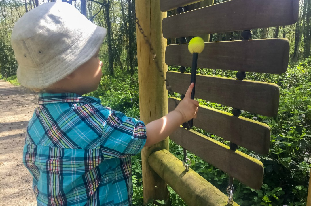 A little boy plays on a wooden xylophone at Pepenbury Woodlands in Kent- Our Weekend Happy 13: Country Parks, Woodland Walks and a Party - Mrs H's Favourite Things