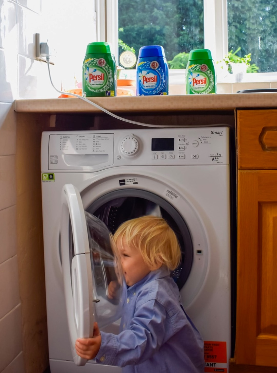 A photograph of a little boy (22 months old) playing with a washing machine - on top of the washing machine are three bottles of Persil Powergems - Sharing My Laundry Gems With Persil Powergems - Mrs H's favourite things