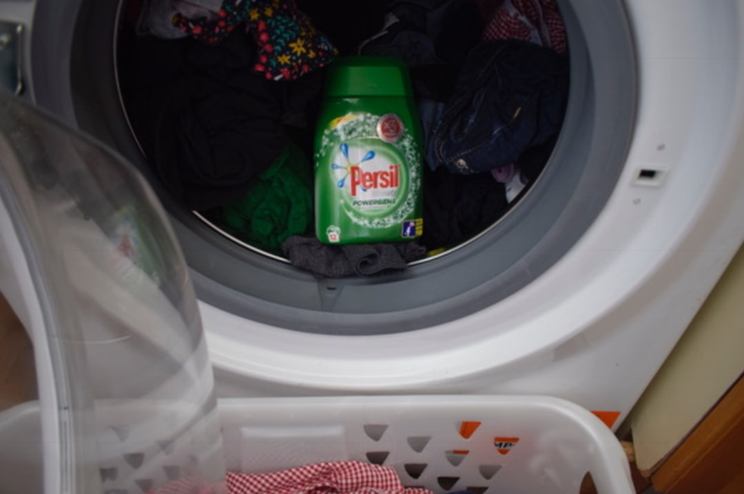 A photograph of a bottle of Persil Ultimate Powergems in a washing machine filled with a dark wash - Sharing My Laundry Gems With Persil Powergems - Mrs H's favourite things