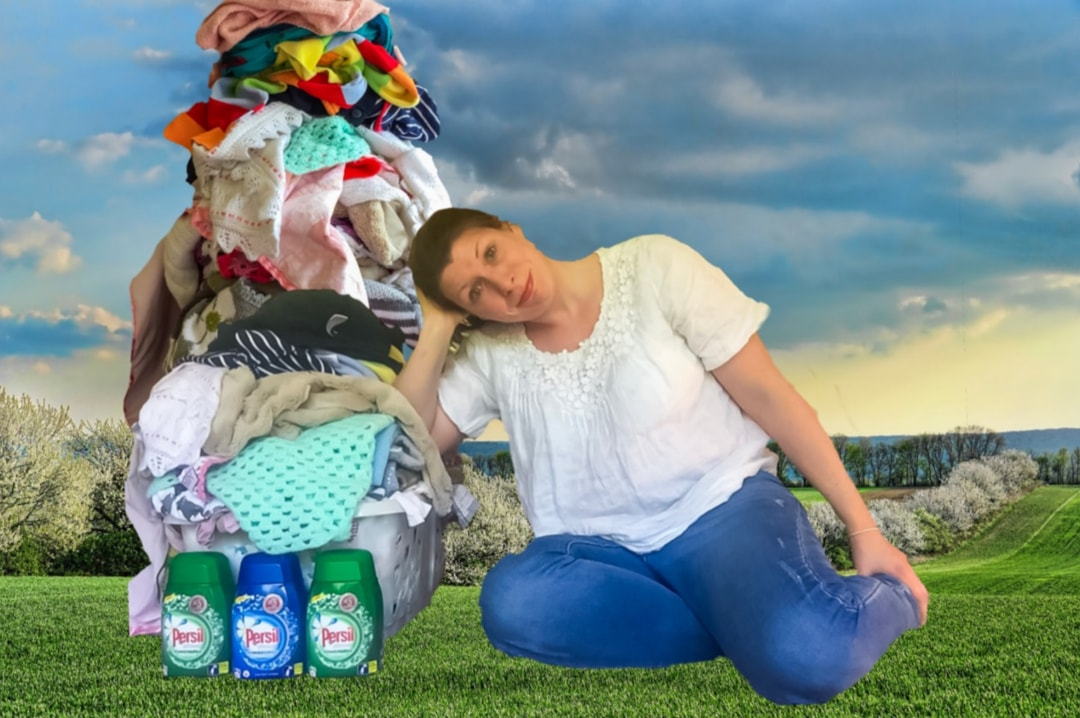 A photograph of a woman leaning against a laundry pile and looking fed up. In front of the laundry pile are three bottles of Persil ultimate Powergems. And using the power of Photoshop the woman is sitting in a field and her laundry pile is so tall it touches up to the ceiling - Sharing My Laundry Gems With Persil Ultimate Powergems - Mrs H's favourite things