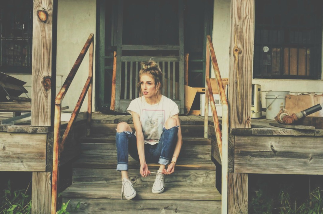 A woman wearing a t-shirt and scruffy jeans sits on the porch of a house in dire need of renovation - These Signs are Telling You That You Need To Move, But Are You listening? - Mrs H's favourite things