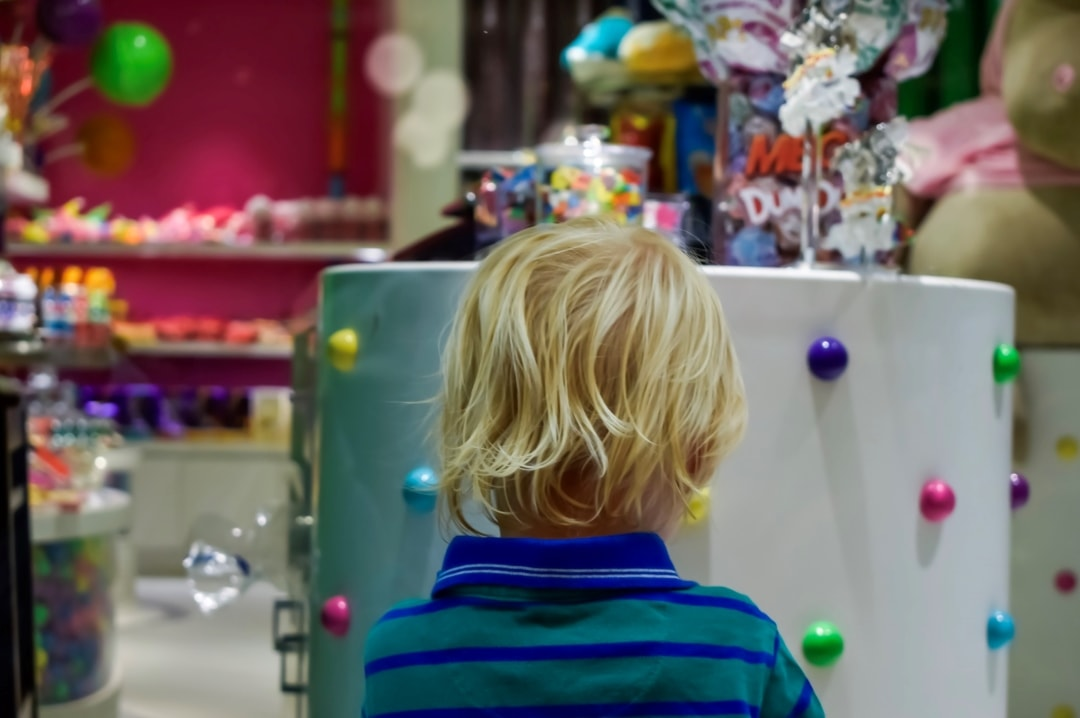 A photograph of a little boy with his face up to the glass of a sweet shop on the Royal Promenade onboard the Royal Caribbean cruise ship Independence of the Seas - 10 Reasons Why A Royal Caribbean Cruise Would Make The Perfect Family Holiday - Mrs H's favourite things