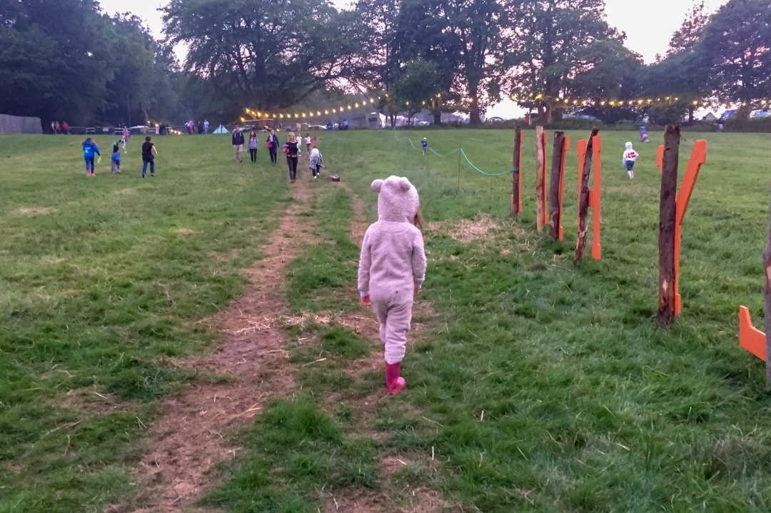 A photograph of a little girl in a bear onesie walking up a hill at Elderflower Fields Festival - Our First Family Festival and Our Festival Essentials - Mrs h's favourite things