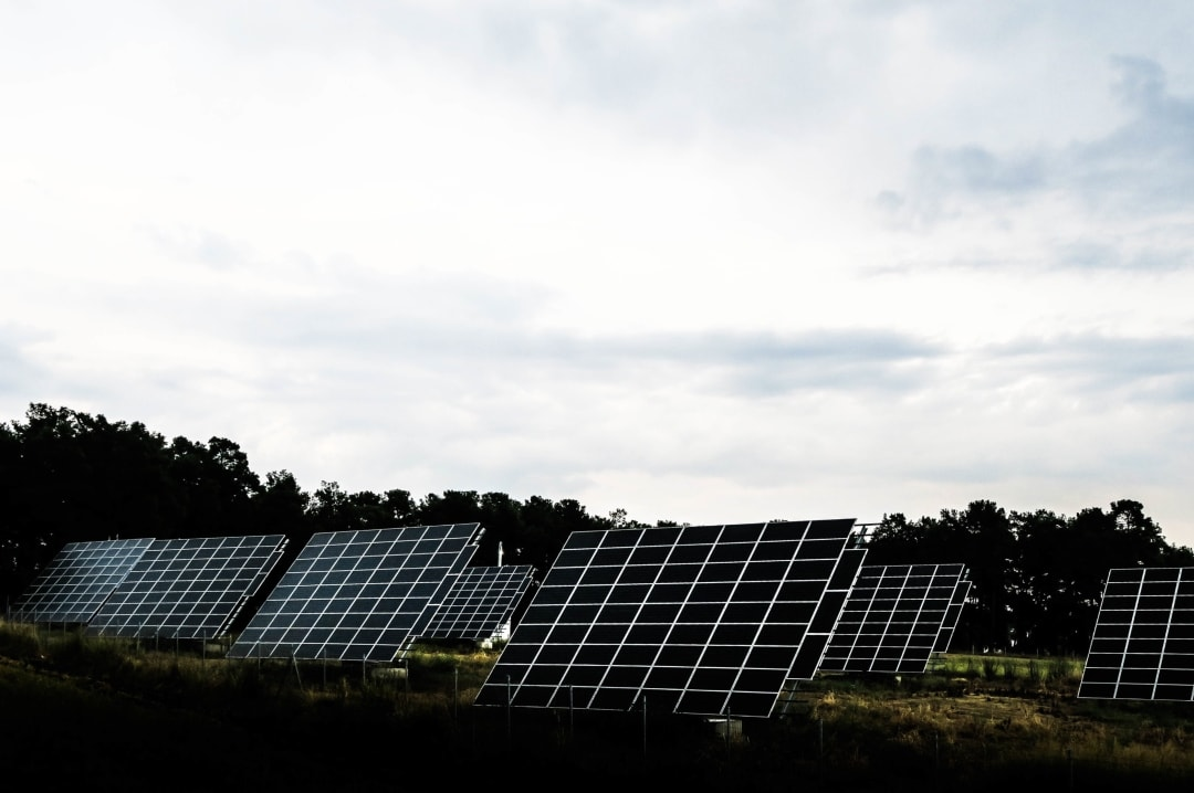 A photograph of some solar panels in a field - Simple Steps To Stop Your House Being An Energy Suck - Mrs H's favourite things