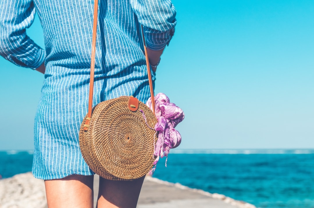 A photograph of a woman walking in the sunshine wearing a shirt dress and a summer handbag - Summer Wardrobe Staples - Mrs H's favourite things