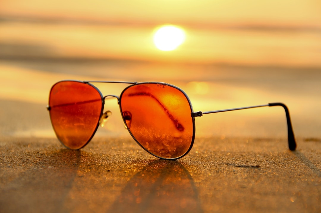 A photograph of a pair of sunglasses on a beach at sunset - Summer Wardrobe Staples - Mrs H's favourite things