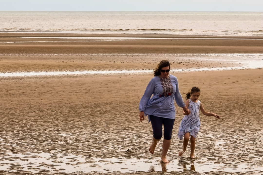 A photograph of a mother hand-in-hand with her daughter running a long Dymchurch Beach - How It Feels To Have A Depression And Anxiety Relapse - Mrs H's favourite things