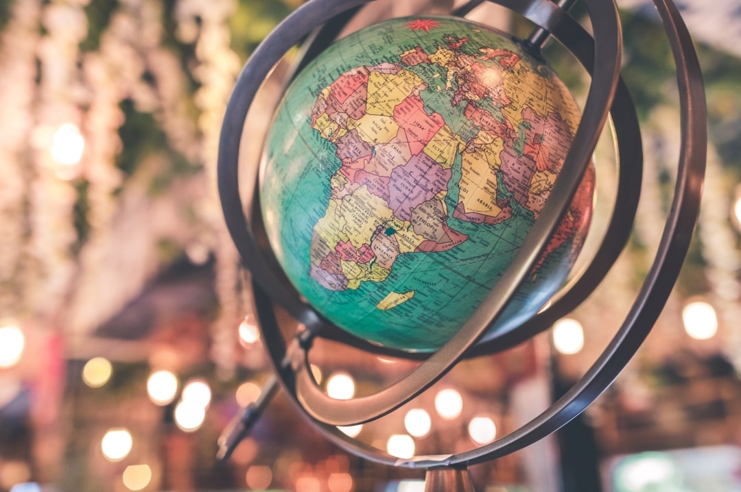A photograph of a globe against some fairy lights -  Is It Time To Tackle Your Travel Bucket List? - Mrs H's favourite things