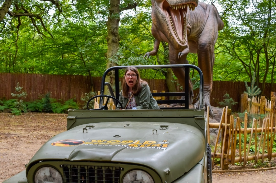 A photograph of a lady in a jeep in front of an animatronic dinosaur from the World of Dinosaurs at Paradise Wildlife Park - Paradise Wildlife Park - A Review - Mrs H's favourite things