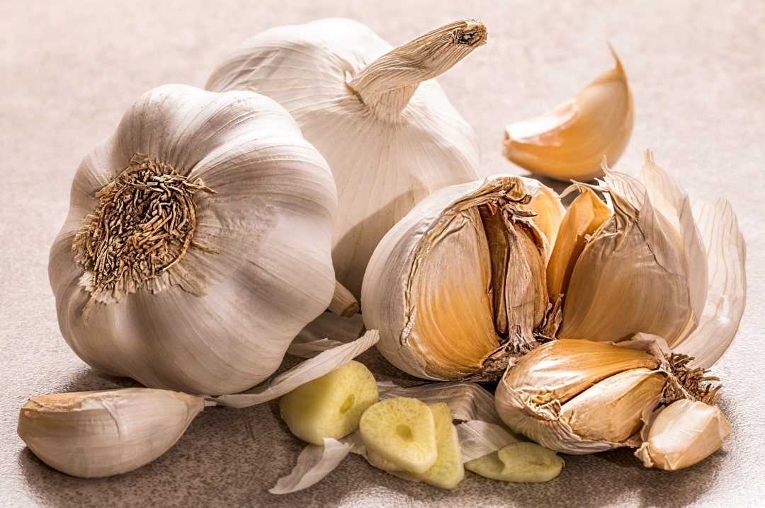 A photograph of some garlic bulbs, and cut up garlic - 7 Foods That Are Great For Your Health - Mrs H's favourite things