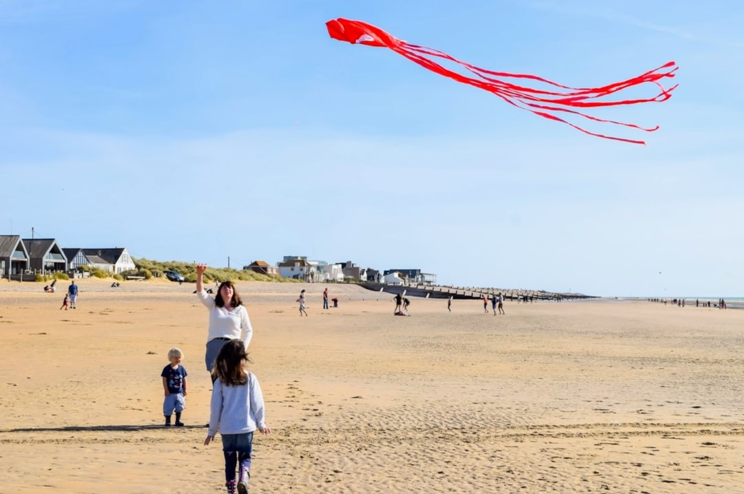 A photograph of a woman and her children flying a kite on a beach on a beautiful sunny day - Finding Happiness And Chasing Rainbows - Mrs H's favourite things