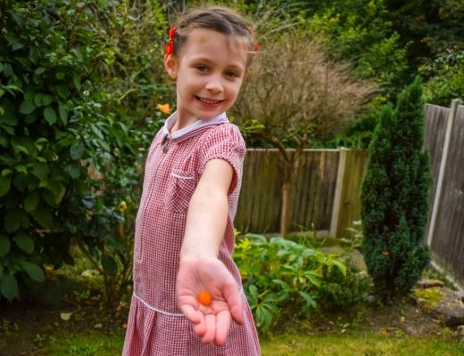 A photograph of a little girl wearing her school uniform and standing in her garden and in her hand she is holding a Bassetts Vitamins Omega-3 + Multivitamins Orange Flavour Pastille - Jumping At The Chance To Try Bassetts Vitamins Omega-3 + Multivitamins Orange Flavour Pastilles _ Mrs H's favourite things