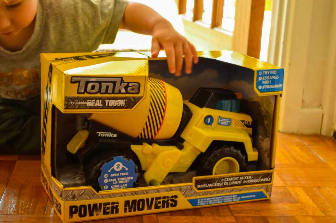 A photograph of a little boy looking at a boxed up toy. It is the Tonka Power Movers Cement Mixer from the Tonka Power Movers Vehicles collection - Tonka Power Movers Vehicles - A Review - Mrs H's favourite things