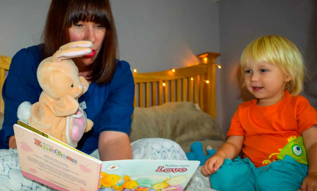 "A photograph of a Mum reading the My First Emotions book ""Robbie feels love"" to her little boy - Feeling The Love With Little Mister H and My First Emotions - Mrs H's favourite things"