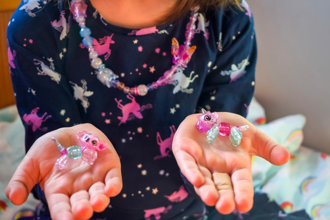 A little girl wearing her Twisty Petz as a necklace and holding two Twisty Petz Babies in her open hands - Twisty Petz CollectAbles From Spin Master - A Review - Mrs H's favourite things
