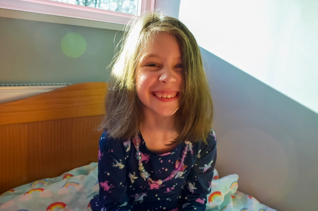 A photograph of a little girl smiling wearing a necklace of Twisty Petz - Twisty Petz CollectAbles From Spin Master - A Review - Mrs H's favourite things