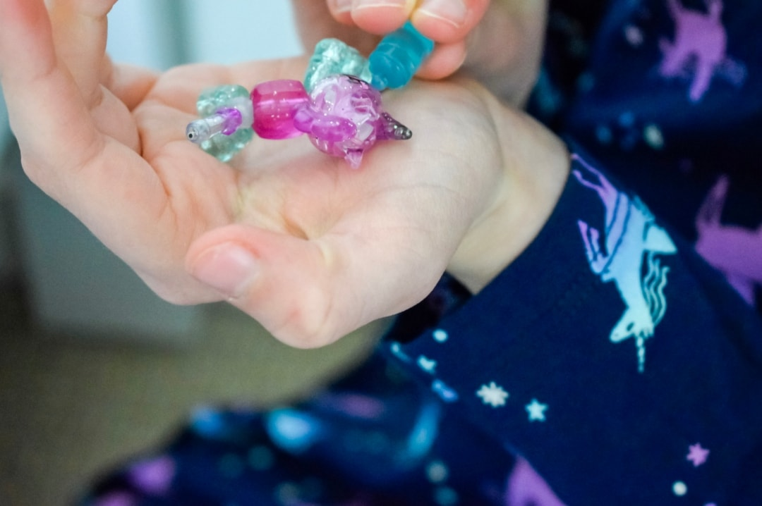 A photograph of a little girl using the blue baby bottle charm to feed her Twisty Petz Babies in her hands - Twisty Petz CollectAbles From Spin Master - A Review - Mrs H's favourite things