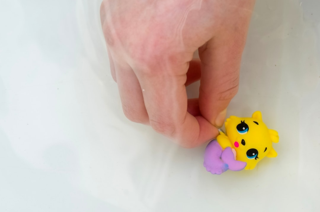 A little girl holding a Hatchimals CollEGGtibles Mermal Magic called Mer-Swotter in warm water to demonstrate the colour change technology - Hatchimals CollEGGtibles Mermal Magic Season 5 Review - Mrs H's favourite things