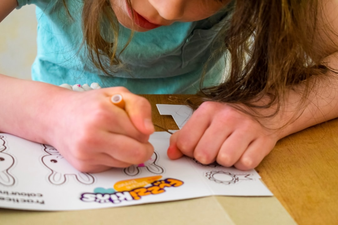A photograph of a little girl drawing the designs of her Fuzzikinz Bedtime Bunnies on the practice sheets that come with the sets - Fuzzikins Bedtime Bunnies Review - Mrs H's favourite things