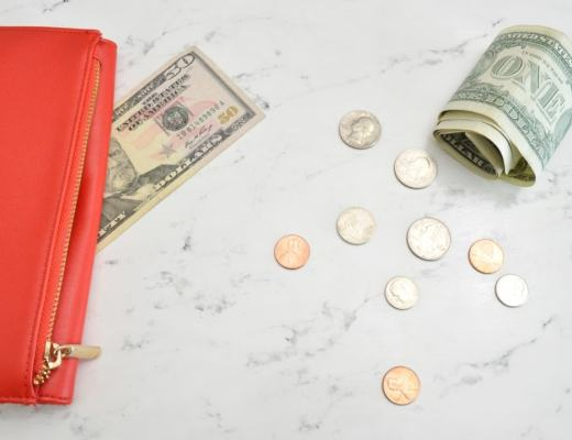 A photograph of a red purse and some dollar bills lying on a white marble table - How To Get Your Money Back On Track Ahead Of The Summer Holidays - Mrs H's favourite things