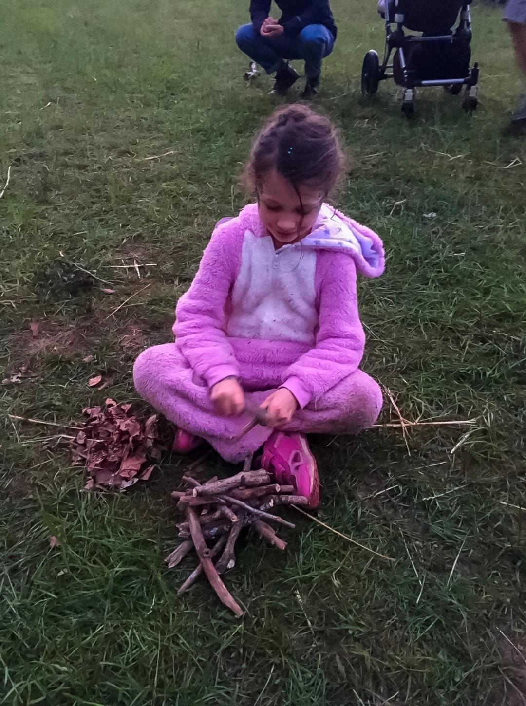 A little girl sitting cross-legged on the ground at Elderflower Fields Festival - Elderflower Fields: The Perfect Family Festival - Part One - Mrs H's favourite things